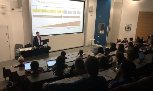 A picture of a lecture theatre with students watching a presentation